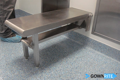 GownRite™ Stainless Steel Wall-Mounted Folding Gowning Bench shown folded down next to clean room tech