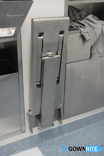 GownRite™ Stainless Steel Wall-Mounted Folding Gowning Bench shown flipped up and stowed in gowning room
