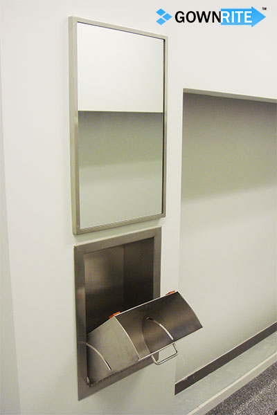 GownRite™ Stainless Steel Wall-Mounted Gowning Mirror shown installed above head cover dispenser